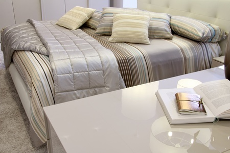 furniture store: Detail of a stylish bedroom with grey sheets . Furniture store