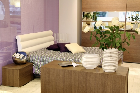 Stylish purple and white bed in modern bedroom with flower decoration . Furniture store photo