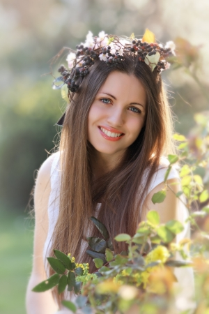 Beautiful smiling girl dressed like a spring nymph with flower crown photo