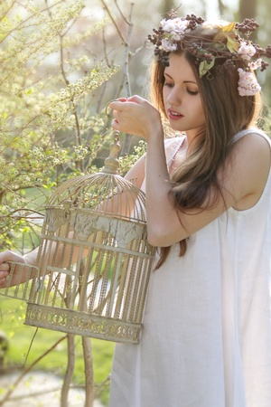 Beautiful spring nymph opening a vintage bird cage. Model wearing a flowers crown photo