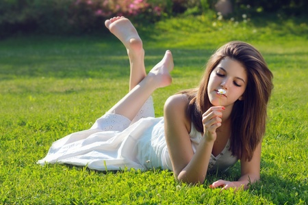 bare feet girl: Pretty young girl with a daisy in hand, lying on grass with bare feet . Purity and relax conceptual