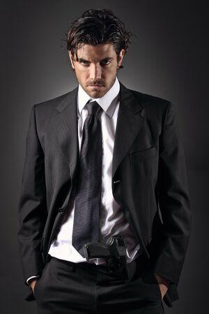 魅力的でエレガントな男の銃彼のズボンでポーズ