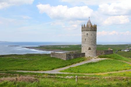 Doonagore castle , irish stone guardian between green fields and sea. Ireland Editorial