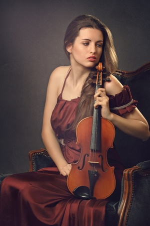 Beautiful girl posing with a fiddle seated on a velvet armchair . Model dressed in red silk and textured backdrop