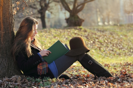 woman reading book: Young beautiful woman reading a book at the park. Autumn season