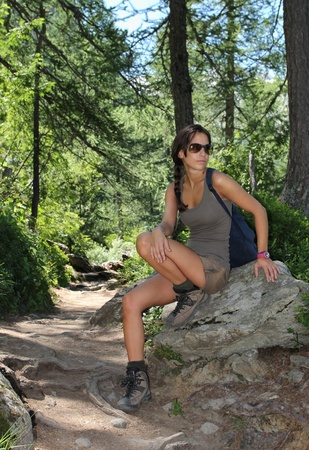 Beautiful hiker girl posing on a rock in the woods photo
