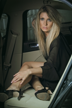 Beautiful elegant woman posing inside a car. Dark toning photo