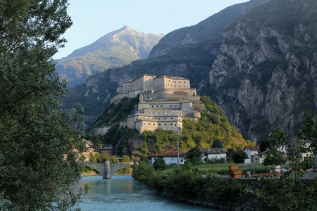 aosta: Bard fortress from the river lighted by sunset light
