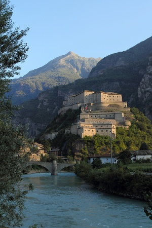 bard: Fortress of Bard in Aosta Valley taken from the river at sunset