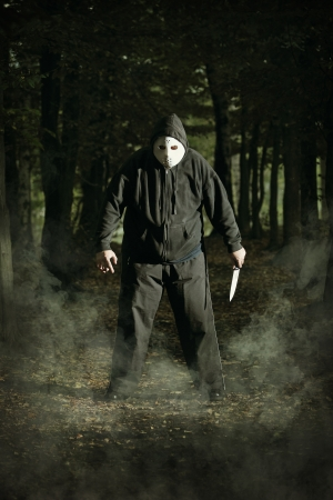 murdering: Masked maniac with knife in the woods   Halloween and horror concept Stock Photo