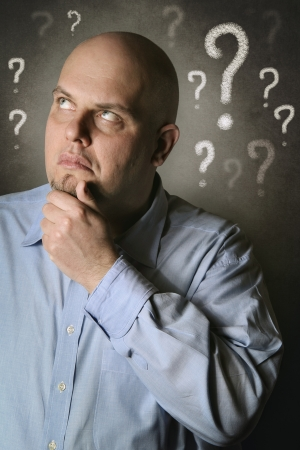 Man pensive and full of doubts . Portrait with grey textured background Standard-Bild
