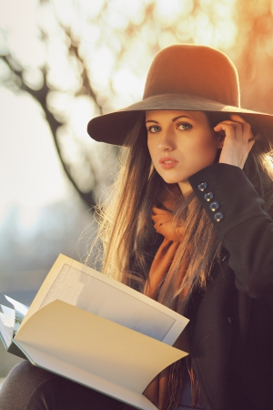 attractive gorgeous: Beautiful and elegant girl poses with a book in warm autumn light