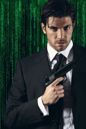 Elegant cyber spy posing with gun in hand  Green matrix background portrait  photo