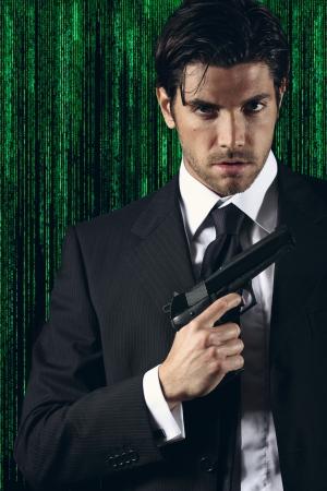 Elegant cyber spy posing with gun in hand  Green matrix background portrait