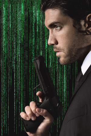 Half portrait of a seductive cyber spy with gun in hand  Studio shot with matrix background Standard-Bild