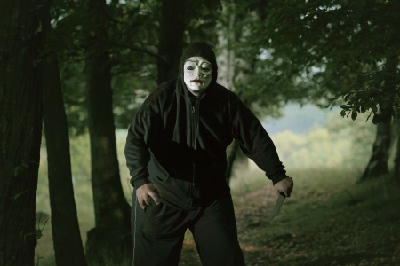 creepy: Masked mad man with a knife in the woods . Halloween concept Stock Photo