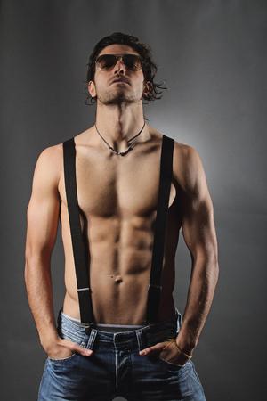 Studio shot van een sexy shirtless man met zwarte bretels. Grijze achtergrond portret Stockfoto