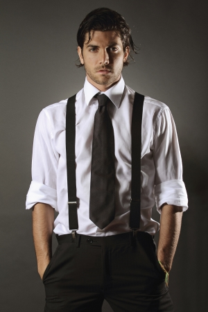 suspenders: Handsome fashion model  with black tie and suspenders . Bold expression
