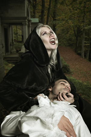 halloween concept: Vampire lady attacks her prey . Horror and Halloween concept