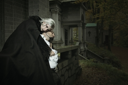 bite: Vampire lady embraces her victim . Horror and Halloween concept