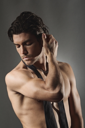Studio shot of a sexy man posing shirtless . Grey backdrop portrait photo