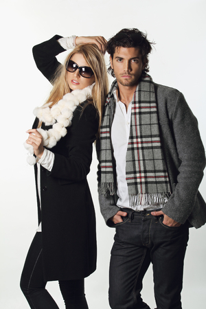 Couple of fashion models wearing winter dress. White backdrop photo