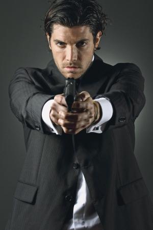 エレガントなドレスを持つハンサムな男は、2 つの手で銃を保持します。 写真素材