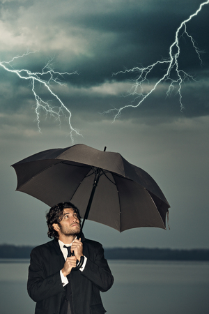 storm coming: Businessman protecting himself from the storm coming with an umbrella. Dark sky with thunders