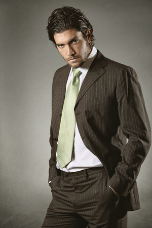resolute: Elegant businessman with resolute gaze in fashion pose . Grey backdrop Stock Photo