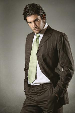 gaze: Elegant zakenman met vastberaden blik op manier stelt. Grijze achtergrond Stockfoto