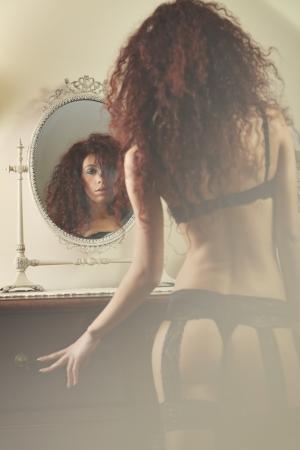 voluptuosa: Reflexión de espejo de una mujer hermosa en ropa interior. Centrarse en la cara Foto de archivo