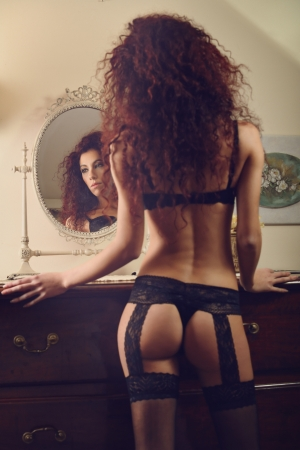 boudoir: Sexy portrait of a lingerie model reflected in the mirror. Focus on face  Stock Photo