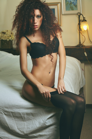 boudoir: Lingerie sensual woman dressing on bed. Boudoir and glamour