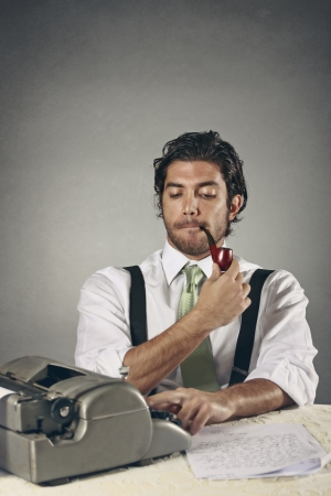Funny expression of an handsome writer with a pipe . Retro style photo
