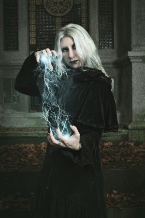 mage: Dark mage is casting a lighting bolt spell . Halloween and fantasy Stock Photo