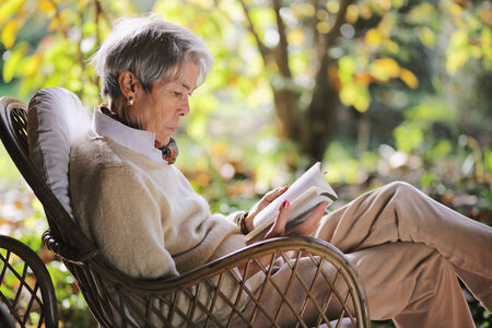 Senior lady is relaxing outdoor reading a book in the garden