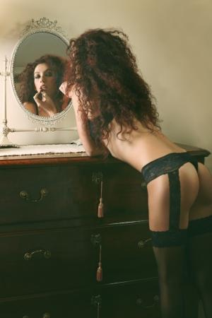 boudoir: Beautiful brunette model make up in front of the mirror . Glamour and boudoir  Stock Photo