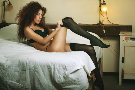 boudoir: Beautiful brunette woman dressing on bed. Boudoir and glamour