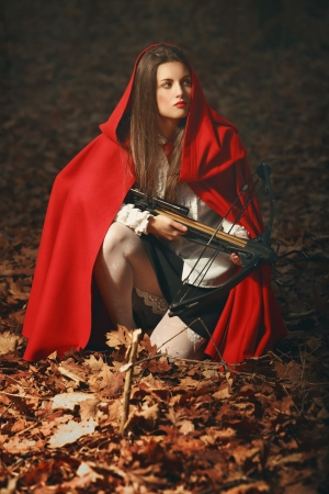 Fashion little red riding hood posing in the forest with a crossbow  like an hunter photo