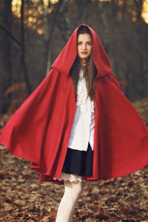 Little Red riding hood posing in the forest with flying mantle photo