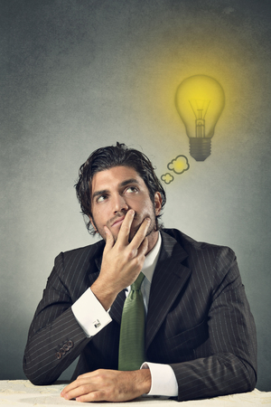 Portrait of a businessman with a lighted lamp bulb    Idea and creativity concept photo