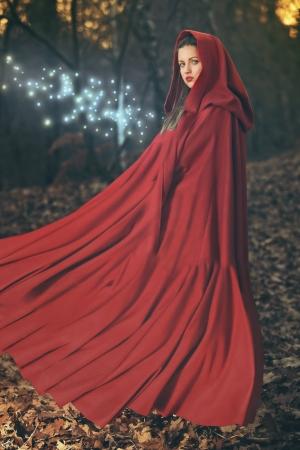 Mooie vrouw met rode vliegende mantel poseren in het bos