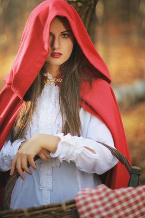 caperucita roja: Retrato de la hermosa caperucita roja con la cesta de mimbre en el bosque