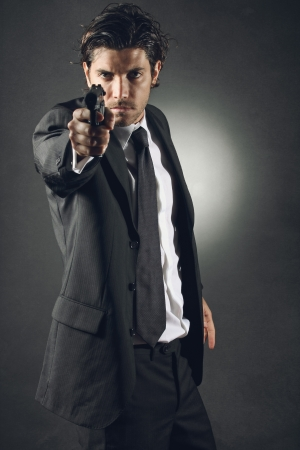 Handsome bodyguard  with elegant dress aiming . Dark toning
