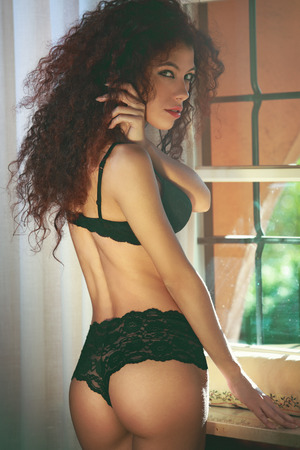 boudoir: Attractive model posing in black lingerie close to the window