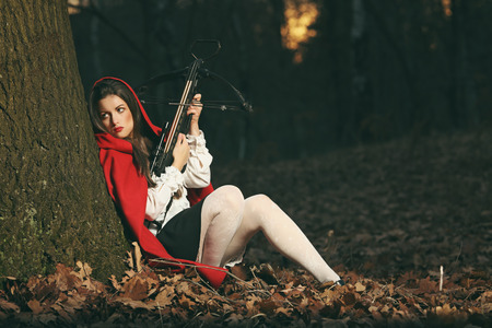 crossbow: Little red riding hood leaning to a tree in the forest with a crossbow. Wolf hunter Stock Photo