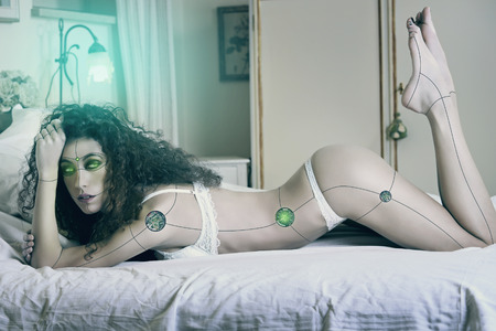 Sexy cyborg woman posing on bed . Sci fiction and technology conceptual