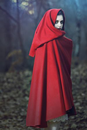 숲에서 빨간 망토 포즈와 아름 다운 여자의 어두운 초상화. 환상과 마법