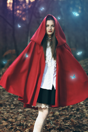 Beautiful fantasy portrait of a girl dressed in red cloak among magical butterflies  photo