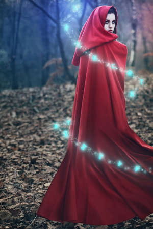 Fantasy beautiful woman with red flying cloak and swirling runes around